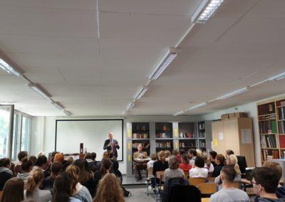 Herr Mieles begrüßt die Schüler*innen und Herrn Mosebach in der Schulbibliothek
