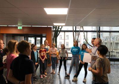 Fenja B., Liora M. mit der 6b, Herrn Gabriel und Herrn Mieles bei der Checkübergabe an Frau Mosbach im Foyer des Lessing-Gymnasiums